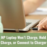Hand plugging power adapter into laptop